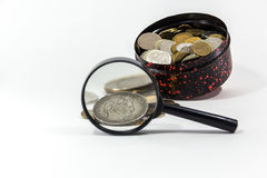 Silver coin under a magnifying glass. Silver coin under a magnifier on a background of a box with coins royalty free stock images
