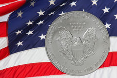 Silver Coin and USA Flag. American Silver Eagle coin, with the United States flag waving in the background Stock Photography