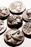 Silver coins of ancient Greece on reflective surface Stock Photo