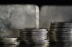 Silver Coins infront of Silver Bars.  royalty free stock photography