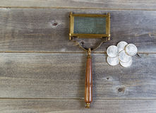 Silver Coins and Magnifying Glass on Wood Stock Photo