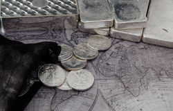 Silver Coins and Silver Bars on top of Map.  royalty free stock photo