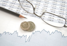 Silver coins on top of line chart and spreadsheet. With glasses and pencil Royalty Free Stock Photo