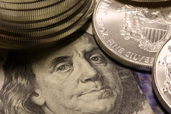 Silver coins on top of a one hundred dollar bill Stock Images