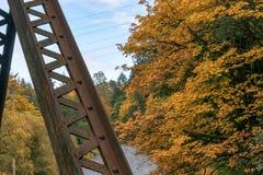 Rusty support above river. Silver colored bridge over bright autumn river Stock Image
