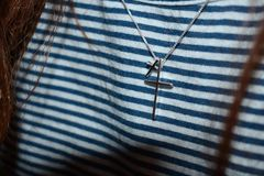Silver-colored Cross Pendant on Black and White Stripe Textile Stock Photography