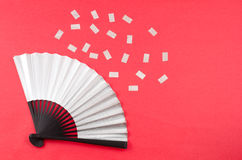 Silver colored folding fan and confetti Royalty Free Stock Image
