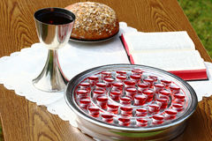 Silver communion cups, bread and Bible. Royalty Free Stock Photography