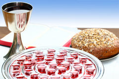 Silver communion ware with open Bible and bread Stock Image