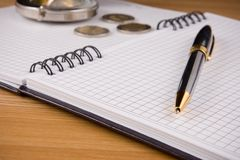 Silver compass and pen at notebook on woo Stock Images