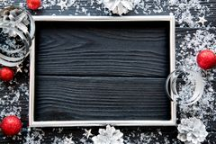 Silver cones, silver frame, silver ribbons and red Christmas balls on black table. Space for text. royalty free stock photo