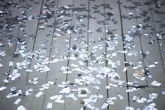 Silver confetti scattered on a white wooden floor.New year party. Silver confetti scattered on a white wooden floor. New year party stock photography