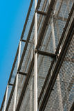 Silver corrugated metal wall seen from below with clear blue sky Stock Photo