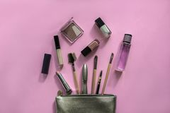 Silver cosmetic bag with makeup products on pink background. Set of decorative beauty accessories for woman. Top view, flat lay.  stock image