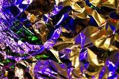 Silver crampled foil background. Lit with colorful lights. Texture of simple metal foil. Multicolored holographic backdrop royalty free stock images