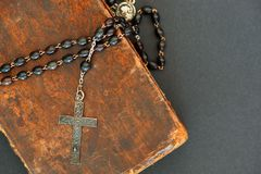 Silver cross on ancient Holy Bible. Old silver cross with black beads on an ancient book (Holy Bible Stock Images