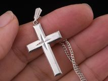Silver cross and chain in hand, Christian jewelry symbol. Black background. Female hand ccloseup Stock Photo