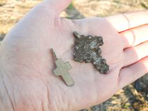 Silver cross in hand found while metal detecting stock photography