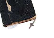 Silver cross on old bible with leather cover Royalty Free Stock Images