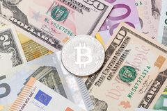 SIlver cruptocurrency bitcoin on dollar and euro background. High resolution photo Royalty Free Stock Image