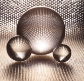 Silver crystal glass balls. Close up of three different sized silver crystal glass balls with textured foil background Royalty Free Stock Image