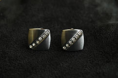 Silver cufflinks on the black matter. Silver cufflinks with rhinestone on the black matter at the center Stock Photos