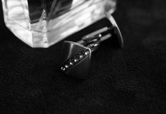 Silver cufflinks next to the perfume bottle. Silver cufflinks with rhinestones on a black background next to the perfume bottle, the horizontal black-and-white Royalty Free Stock Image