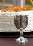 Silver cup. Silver goblet of wine and cake Royalty Free Stock Photography