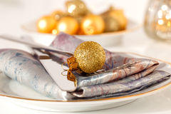 Silver cutlery decorated with a golden Christmas bauble Royalty Free Stock Image