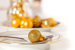 Silver cutlery decorated with a golden Christmas bauble Royalty Free Stock Photography