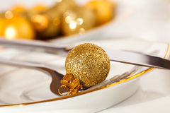 Silver cutlery decorated with a golden Christmas bauble Stock Images