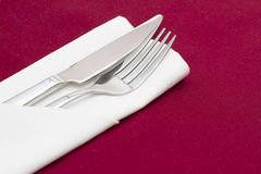 Silver cutlery in folded white napkin Royalty Free Stock Image