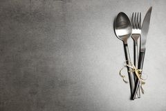 Silver cutlery on gray background, top view. Table setting stock photo