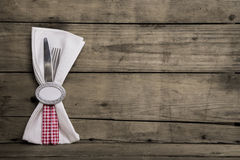 Silver cutlery in red and white checked with napkin on an old wo. Cutlery in red and white checked with napkin on an old wooden background Royalty Free Stock Photos