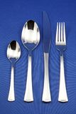Silver cutlery set. Silver cutlery arranged against a blue background Royalty Free Stock Photos