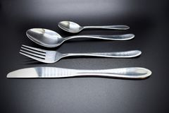 Silver cutlery set against dark background with a soft shadow stock photo