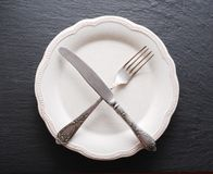 Silver cutlery  and vintage plate on a dark background. Royalty Free Stock Photo