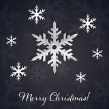 Silver 3D snowflakes on the dark winter and New Year background with snowflake silhouettes. Merry Christmas text on the elegant and minimal black background Stock Images