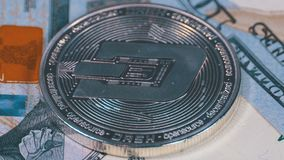 Silver Dash Coin Cryptocurrency and Bills of Dollars are Rotating. Close-up. Macro. Dollar banknotes of various denominations on which lies the crypto currency stock video