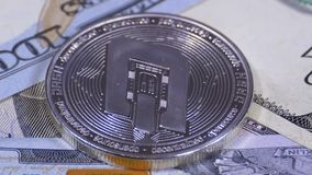 Silver Dash Coin Cryptocurrency and Bills of Dollars are Rotating. Close-up. Macro. Dollar banknotes of various denominations on which lies the crypto currency stock video footage