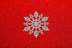 Silver decorative snowflake. On red glitter christmas background Stock Photos