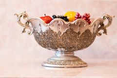 Silver decorative vase with fruits and berries stock photography