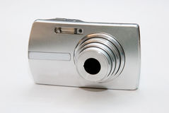 Silver Digital Camera On White Background. Handy digital camera on bright background. switched on to zoom out the lens Royalty Free Stock Photography