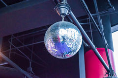 Silver disco ball in nightclub. Silver disco ball with stars in nightclub with striped violet and black walls Stock Image