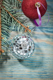 Silver disco bauble red Christmas ball pine brunch on wooden boa. Rd holidays concept Royalty Free Stock Photography