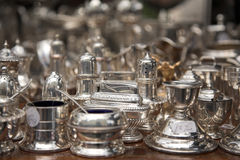 Silver dishes on market table. Miscellaneous silver dishes for sale Stock Images