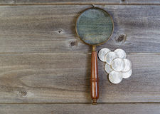 Silver dollar coin collection and round vintage magnify glass on Royalty Free Stock Image