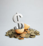 Silver dollar sign hatching from a brown egg. Royalty Free Stock Photos