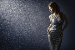 Silver dress, fashion model posing in sparkling gown. Elegant woman beauty portrait on lighting sparkles background stock image