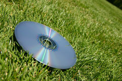 Silver DVD on green grass. Silver rainbow dvd on green grass outside in the sunshine Stock Photos
